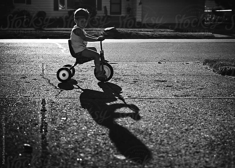 child rides tricycle by Maria Manco for Stocksy United