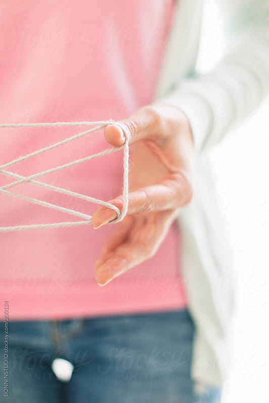 Close-up of woman with pink shirt playing with Cat's cradle game. by BONNINSTUDIO for Stocksy United