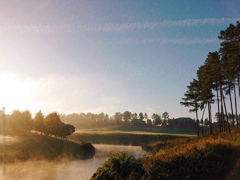 Water hazard on a golf course at sunrise by Joseph West Photography for Stocksy United
