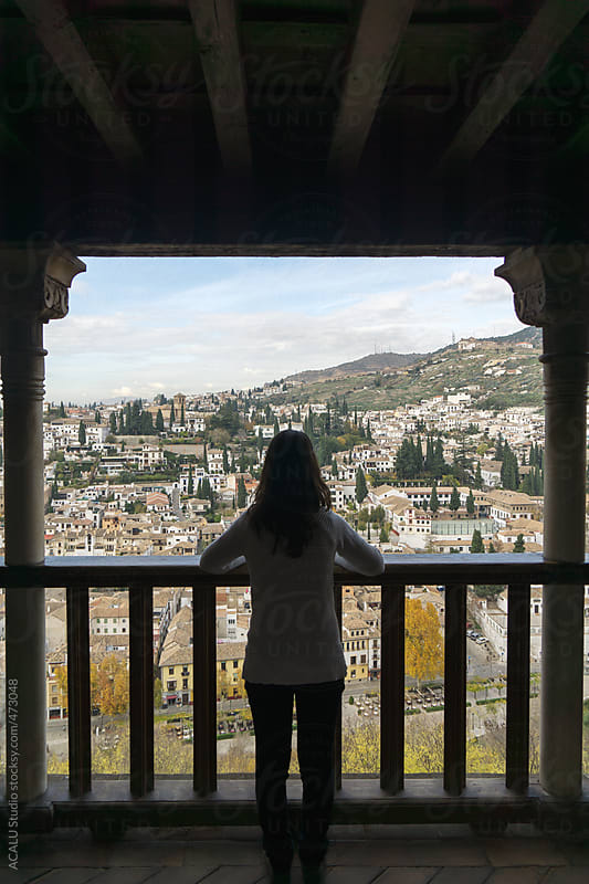 Woman leaning on the balcony admire the view of Granada by ACALU Studio for Stocksy United