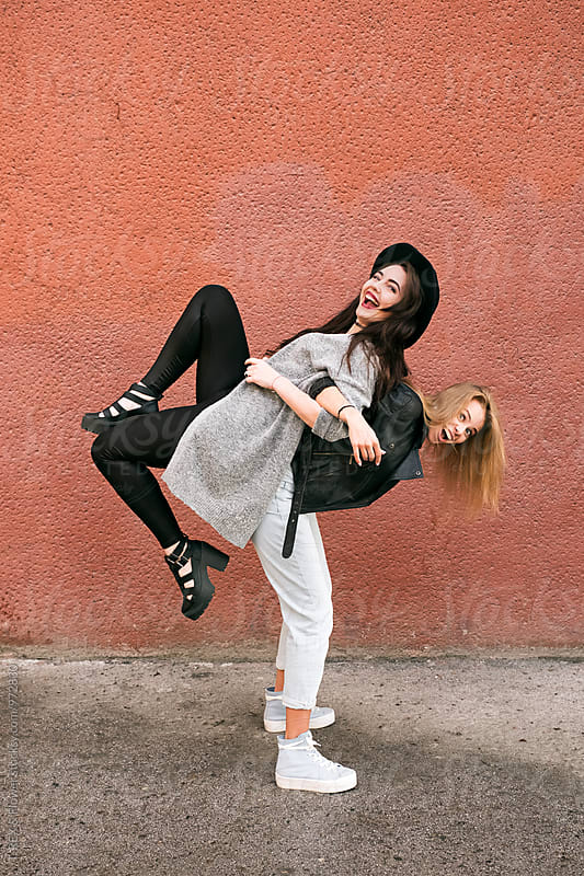 Two girlfriends having fun in the street by T-REX & Flower for Stocksy United