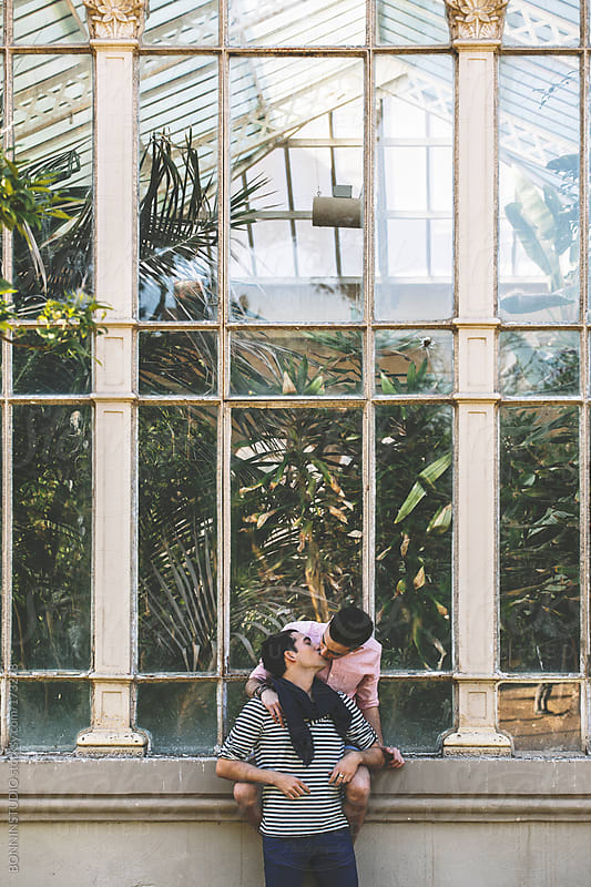 Young gay couple kissing in front a greenhouse.  by BONNINSTUDIO for Stocksy United