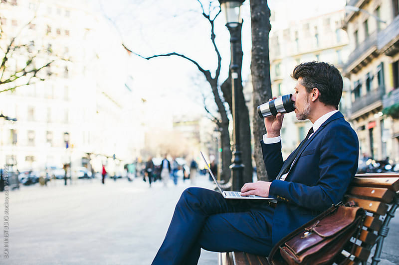 Mature businessman drinking coffee using laptop on the street. by BONNINSTUDIO for Stocksy United