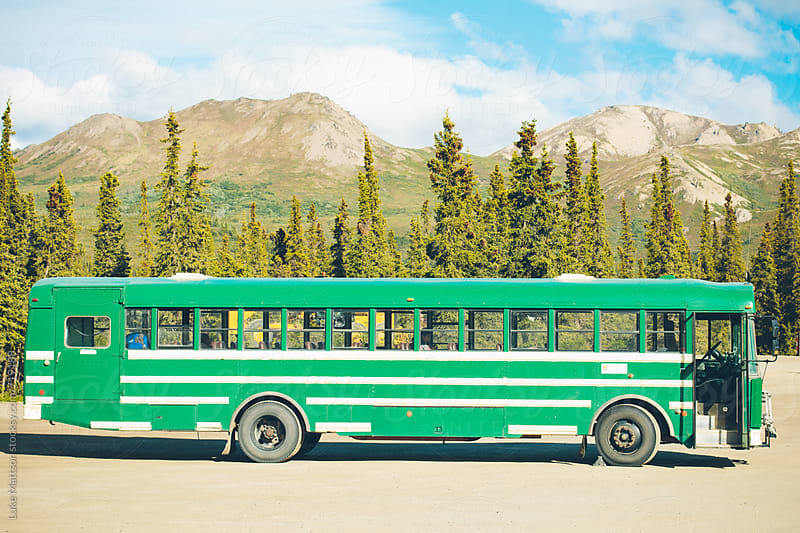 A Green Tour Bus Parked In Front Of A Row Of Forest Trees by Luke Mattson for Stocksy United