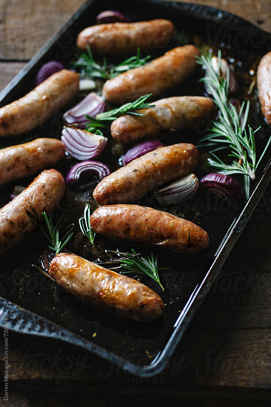 Cooked sausages with red onion and rosemary on a roasting tray. by Darren Muir for Stocksy United