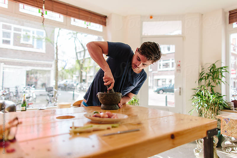 Young man cooking asian food by Denni Van Huis for Stocksy United