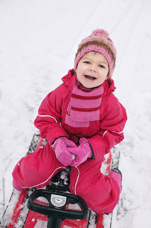 Little girl having fun on a sledge making a snowball and laughing. by Lea Csontos for Stocksy United