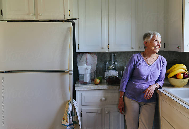 Portrait of senior Woman at Home in Kitchen by Raymond Forbes LLC for Stocksy United