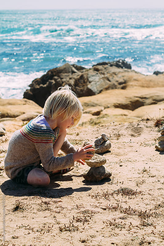 girl stacking stones near ocean by Jess Lewis for Stocksy United