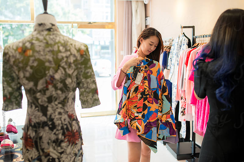 Young business owner helping customer at clothing store by MaaHoo Studio for Stocksy United