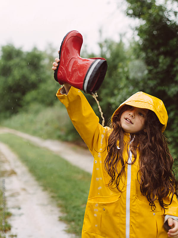 Playful girl pouring rain water from boots. by Dejan Ristovski for Stocksy United