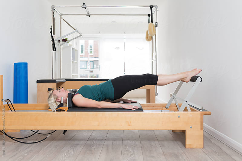 Stretching exercise on a Pilates Reformer. Cadillac in background. by Paul Phillips for Stocksy United