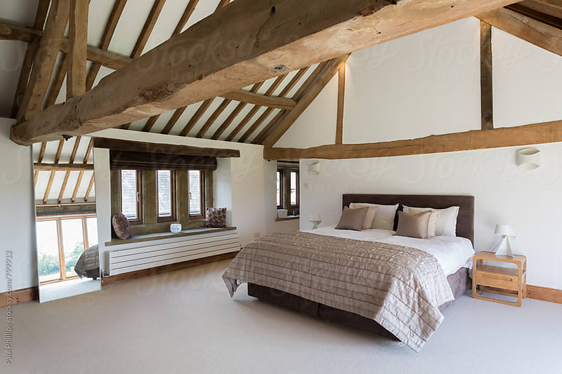 Bedroom in a converted barn showing timber by Paul Phillips for Stocksy United