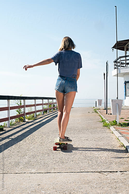 Back view of young girl longboarding  at pier by Danil Nevsky for Stocksy United