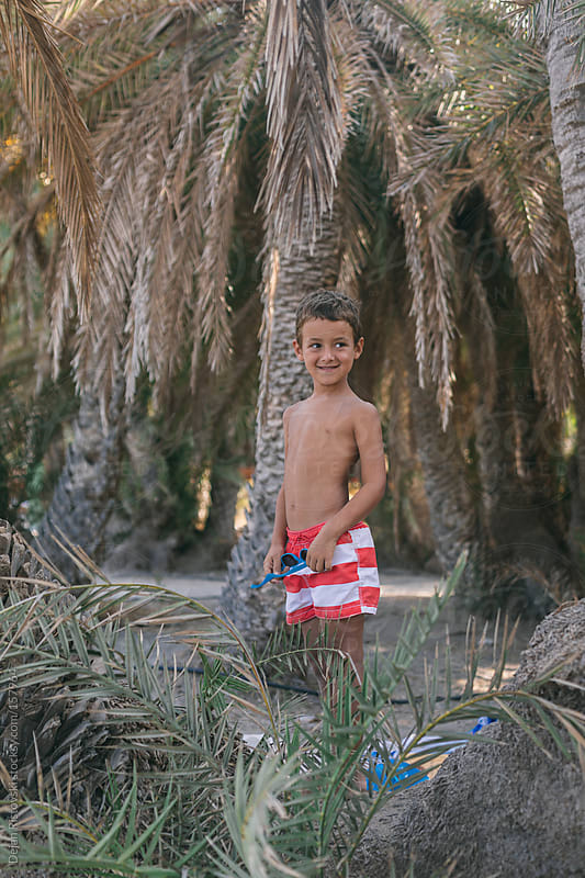 Boy standing on a palm tree by Dejan Ristovski for Stocksy United