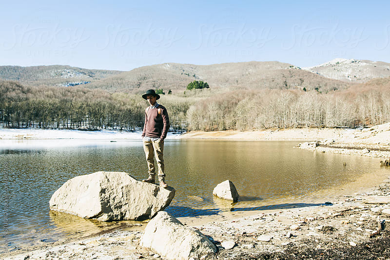 Mountaineer enjoying the nature standing on rock near a lake. by BONNINSTUDIO for Stocksy United