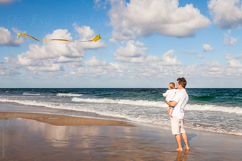 Dad Holds Toddler in His Arms And Flies a Kite on the Beach by Shelly Perry for Stocksy United