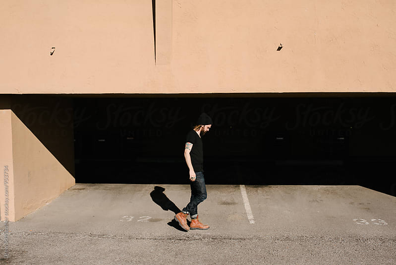 Young man walks in parking garage  by Drew Schrimsher for Stocksy United