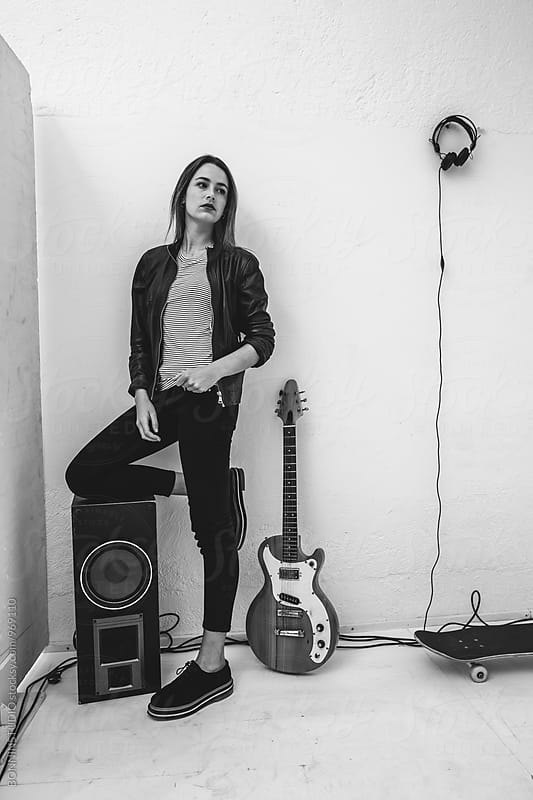 Rocker standing with her electric guitar in recording studio. by BONNINSTUDIO for Stocksy United