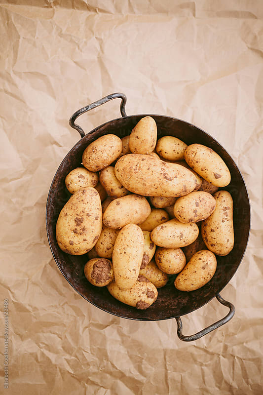 Unpeeled and oncooked new potatoes in an old cooking pot by Elisabeth Coelfen for Stocksy United