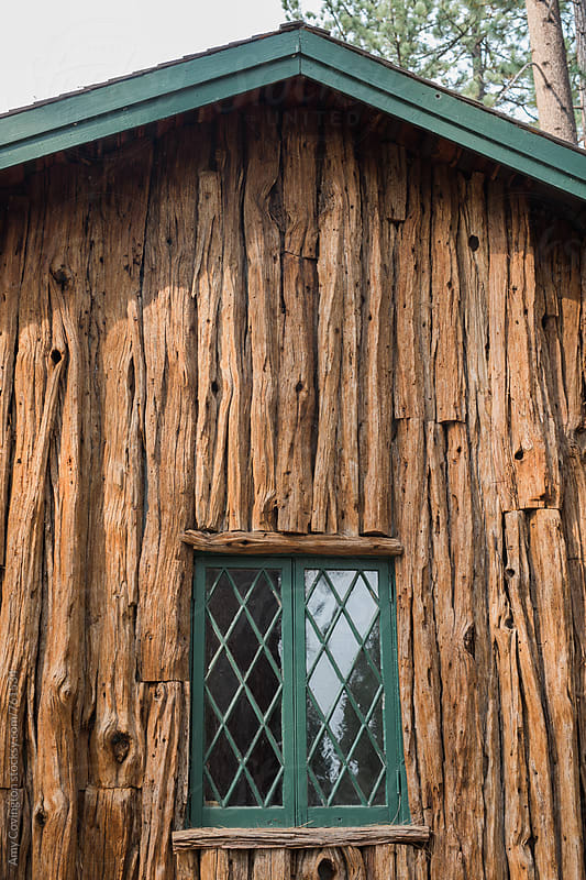 Close up of a cabin with green window and redwood siding  by Amy Covington for Stocksy United