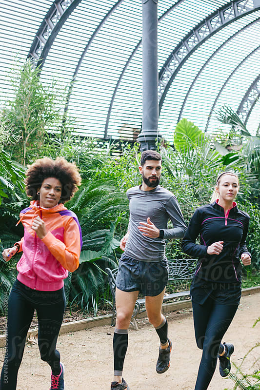 Group of friends running in a greenhouse.  by BONNINSTUDIO for Stocksy United