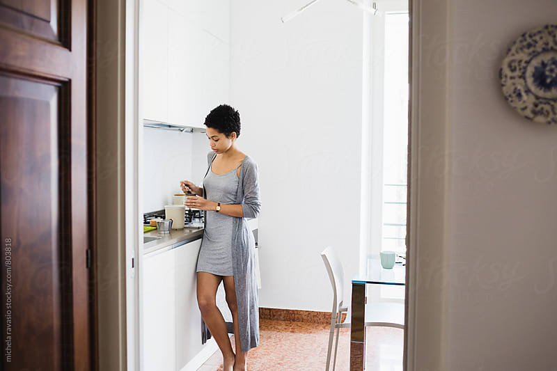 Beautiful young woman preparing coffee at home by michela ravasio for Stocksy United