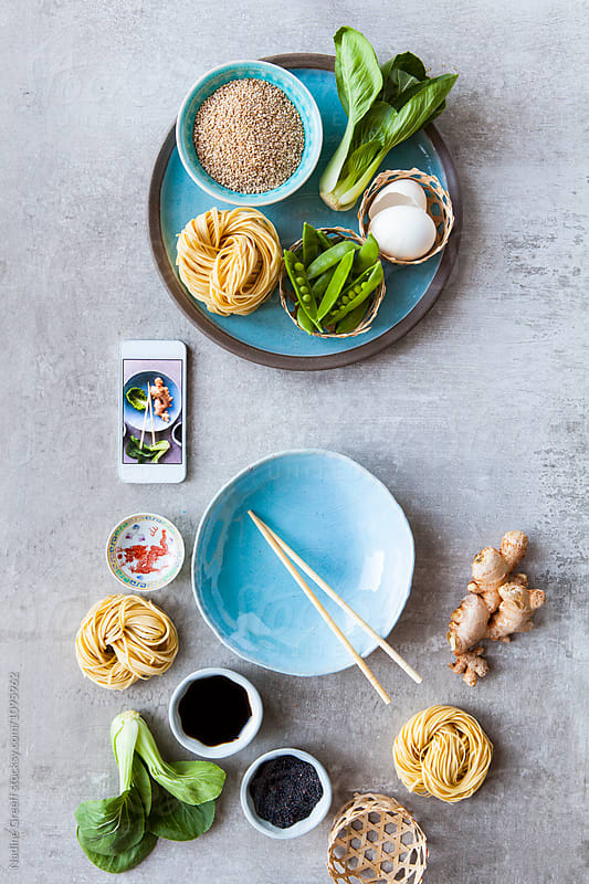 Smartphone with photo of asian cooking ingredients by Nadine Greeff for Stocksy United