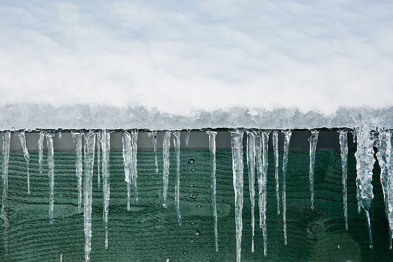 Icicles frozen and hanging on rooftop by Curtis Kim for Stocksy United