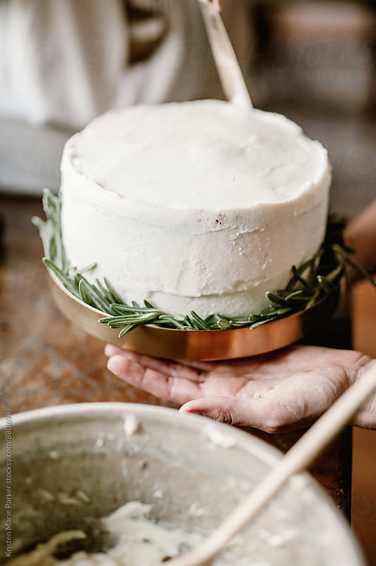 Females decorate homemade cake with white icing and rosemary by Kristen Marie Parker for Stocksy United