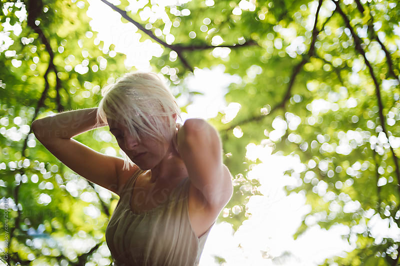 Young woman portrait against green leaves by GIC for Stocksy United