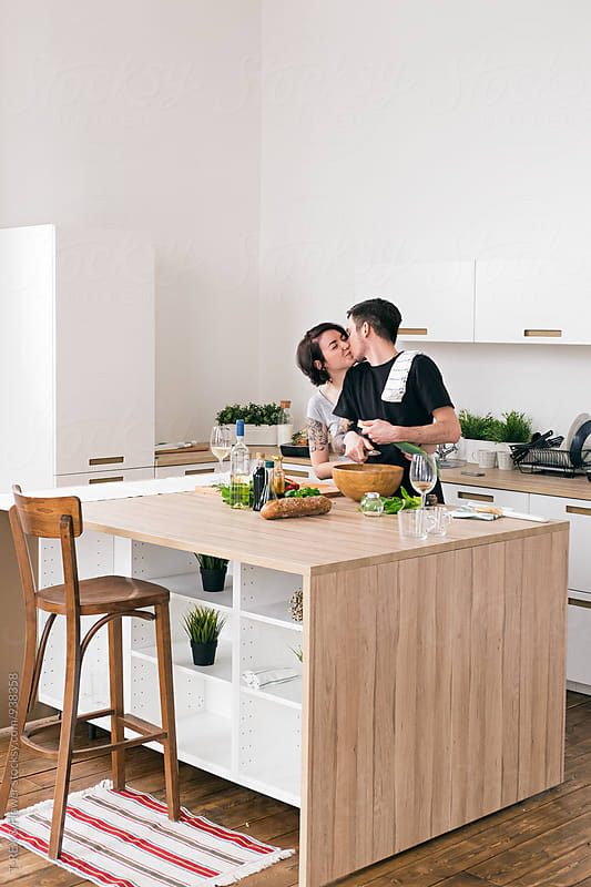 Young couple kissing in the kitchen while cooking by T-REX & Flower for Stocksy United