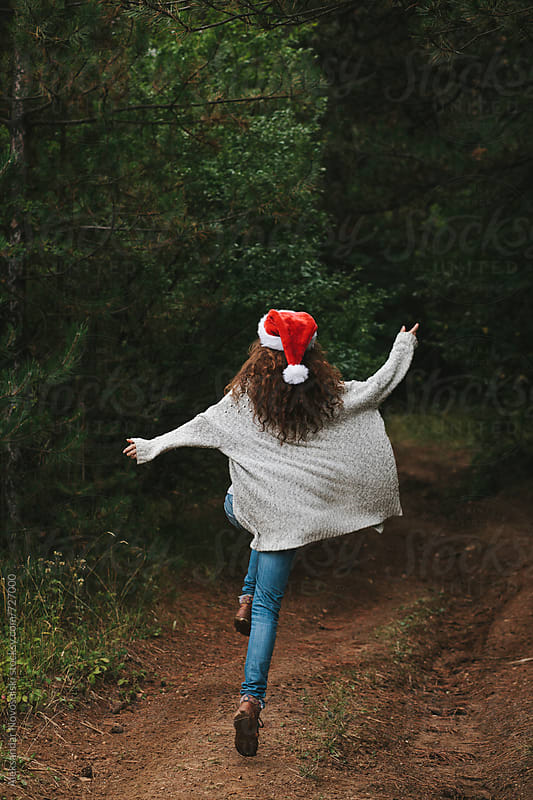 Joyful young woman with christmas hat jumping in the forest by Aleksandar Novoselski for Stocksy United