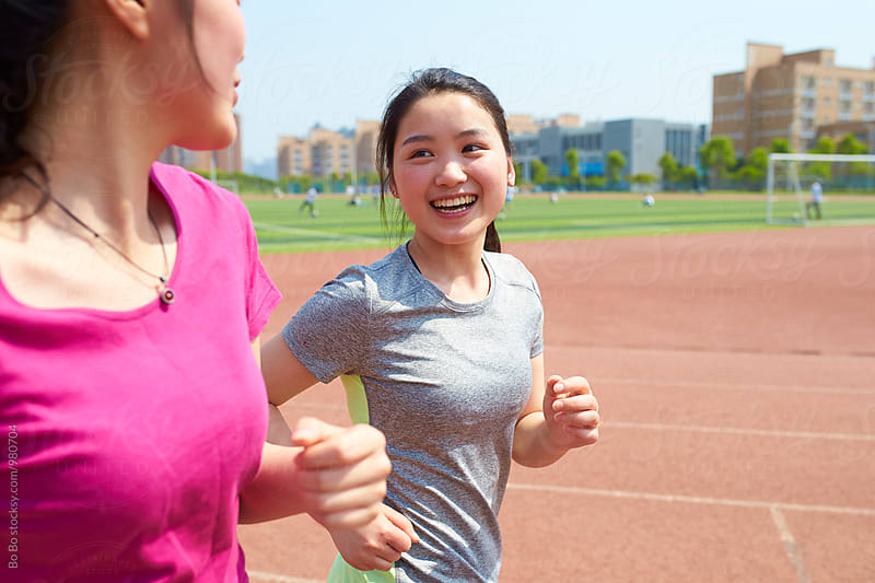 two young asian woman running outdoor by Bo Bo for Stocksy United