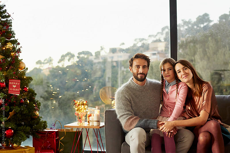 Happy Family Sitting On Sofa By Christmas Tree by ALTO IMAGES for Stocksy United