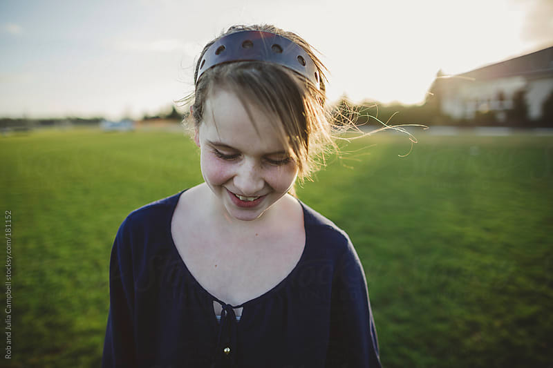 Cute middle school aged caucasian girl happy in windy field  by Rob and Julia Campbell for Stocksy United