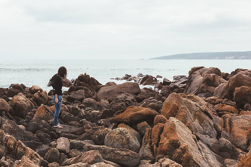 Woman with dark hair stands on rocks by the ocean on an overcast day by Jacqui Miller for Stocksy United