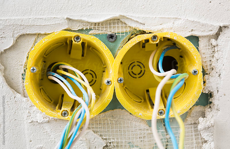 yellow power socket under construction in closeup by Vesna for Stocksy United