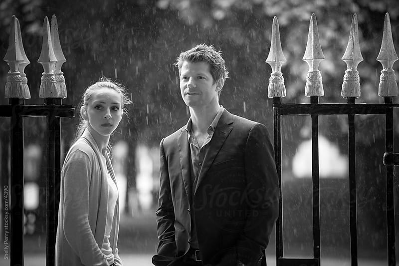 Couple standing at the gates of a garden in Paris by Shelly Perry for Stocksy United