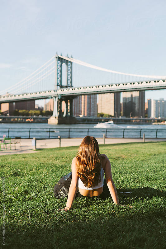 Brunette sitting in the grass in New York by Good Vibrations Images for Stocksy United