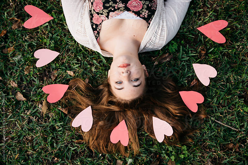 Pink paper hearts around a girl laying in the grass by Gabriel (Gabi) Bucataru for Stocksy United