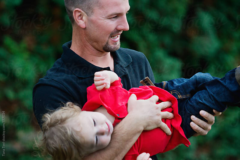 father holds son playfully by Tana Teel for Stocksy United