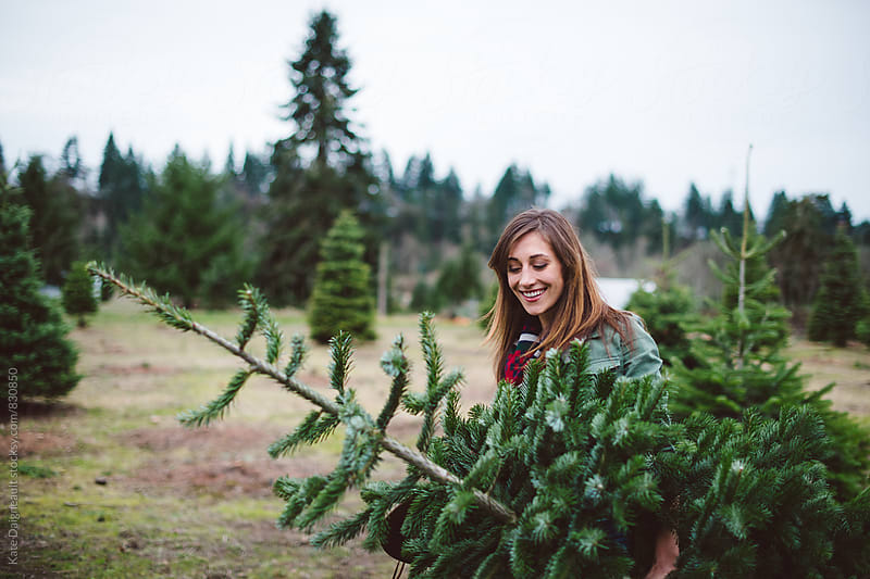 Attractive young woman smiling and carrying christmas tree. by Kate Daigneault for Stocksy United
