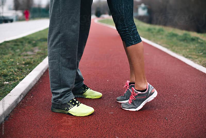 Couple in sportswear standing on jogging track by Marija Mandic for Stocksy United