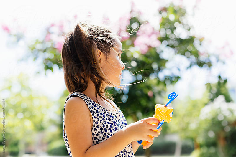 Young girl in park blowing bubbles in the sun. by Image Supply Co for Stocksy United