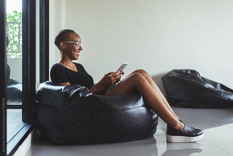 African American Woman in a Bean Bag Using Tablet by Nemanja Glumac for Stocksy United