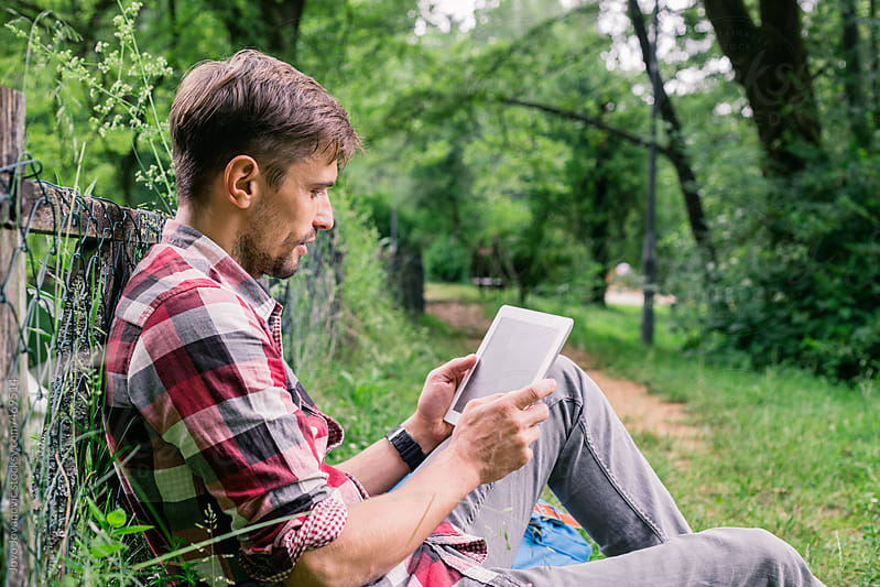 Young man sitting and reading on his tablet at the park by Jovo Jovanovic for Stocksy United