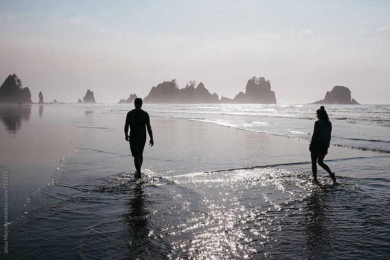 young male and female walk together down beach  by Jesse Morrow for Stocksy United