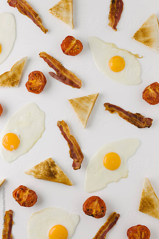 Graphic background with fried egg, bacon, tomato and toast, overhead on white by Kirsty Begg for Stocksy United