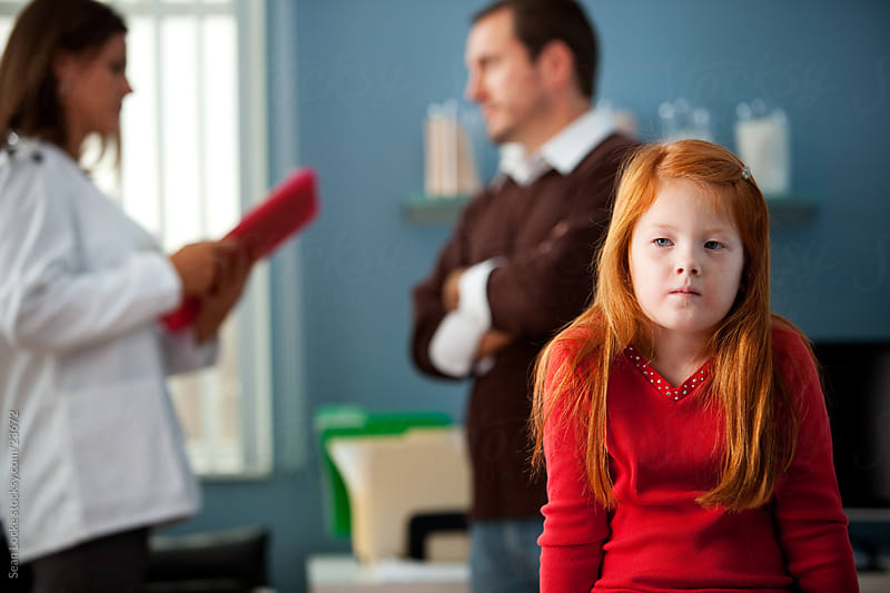 Exam Room: Girl Waits While Parent Discusses with Doctor by Sean Locke for Stocksy United